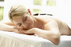 Young Woman Enjoying Hot Stone Treatment Stock Image