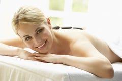 Young Woman Enjoying Hot Stone Treatment Royalty Free Stock Image