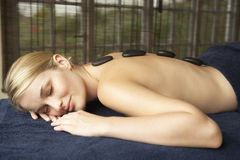 Young Woman Enjoying Hot Stone Treatment Royalty Free Stock Photography
