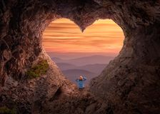 Woman in heart shape cave towards the vast landscape