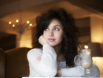 Young woman enjoying latte coffee in cafe Stock Image