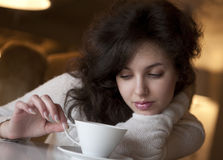 Young woman enjoying latte coffee in cafe Stock Images