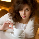 young woman enjoying latte coffee in cafe Stock Photography