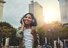 Young woman enjoying listening music on headphone. Cheerful young woman enjoying listening music on wireless headphone through mobile phone in the city royalty free stock photography