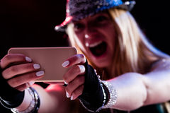Young woman enjoying live entertainment online. Young woman living a live event online using some internet connection or service via her smartphone and feeling stock images