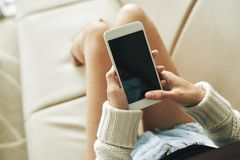 Relaxing on sofa with smartphone Royalty Free Stock Images
