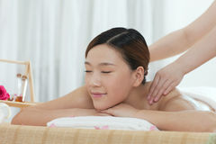 A young woman enjoying massage. A young women enjoying massage at spa salon, indoors Stock Images