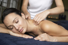 Young Woman Enjoying Massage. With eyes closed Royalty Free Stock Image