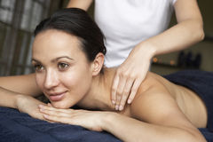 Young Woman Enjoying Massage. Smiling, looking away from camera Royalty Free Stock Photography