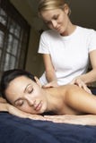 Young Woman Enjoying Massage. Relaxing on bed Stock Photo