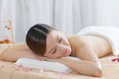 A young woman enjoying massage. At spa salon, indoors Stock Photo