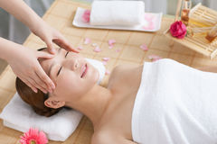 A young woman enjoying massage at spa. A young women enjoying massage at spa, indoors Royalty Free Stock Images