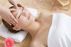 A young woman enjoying massage at spa. A young women enjoying massage at spa, indoors Stock Images