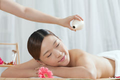 A young woman enjoying massage. A young women enjoying massage at spa salon, indoors Royalty Free Stock Images