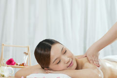 A young woman enjoying massage. A young women enjoying massage at spa salon, indoors Royalty Free Stock Photography