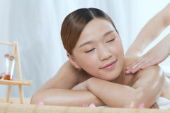 A young woman enjoying massage. A young women enjoying massage at spa salon, indoors Stock Photos