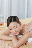 A young woman enjoying massage. A young women enjoying massage at spa salon, indoors Stock Photography