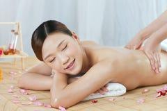 A young woman enjoying massage. A young women enjoying massage at spa salon, indoors Stock Photo