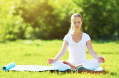 Young woman enjoying meditation and yoga on green grass in summe Royalty Free Stock Images