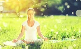young woman enjoying meditation and yoga on green grass in summer on nature stock photos