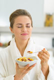 Young woman enjoying muesli in kitchen Royalty Free Stock Photos