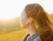 Young woman enjoying a music in the fall season. Autumn outdoor Royalty Free Stock Photos
