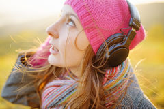 Young woman enjoying a music in the fall season. Autumn outdoor Royalty Free Stock Images