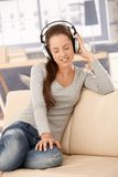 Young woman enjoying music through headphones Stock Photography