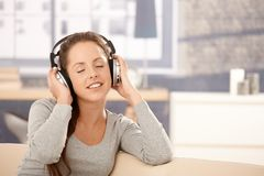 Young woman enjoying music through headphones Stock Photos