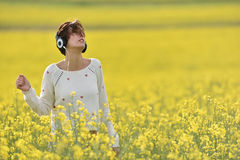 Young woman enjoying music in the headphones in the outdoors Royalty Free Stock Images