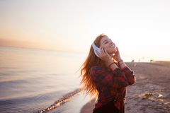 Young woman with headphones, the music lover on the beach Royalty Free Stock Images