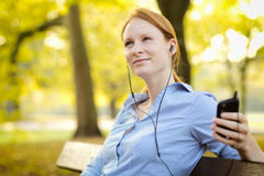 Young Woman Enjoying Music in a Park Royalty Free Stock Images