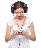 Young woman enjoying music using headphones Royalty Free Stock Images