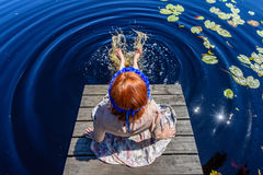 Young woman enjoying nature. On boardwalk in the lake with water lillies and cloud reflections Royalty Free Stock Photography