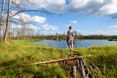 Young woman enjoying nature. On boardwalk in the swamp with photo camera in sunny day Royalty Free Stock Photography