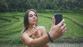 Young woman enjoying the nature in green tropical forest and make selfie with smartphone. Woman enjoying the nature in green tropical forest and make selfie with stock video footage