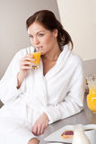 Young woman enjoying orange juice  in kitchen Stock Photography