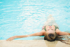 Young woman enjoying pool . rear view Royalty Free Stock Images