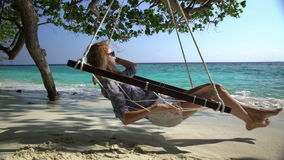 Young woman enjoying a rest in a hammock on the tropical beach. Young woman enjoying a rest in a hammock on the tropical beach to the sound of the surf stock footage