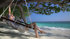 Young woman enjoying a rest in a hammock on the tropical beach. Young woman enjoying a rest in a hammock on the tropical beach to the sound of the surf stock video