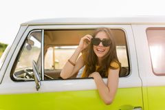 Young woman enjoying a road trip. Young woman in a camper van, smiling Stock Images
