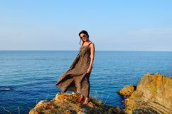 Beautiful Young Woman on a Rocks above the Sea royalty free stock photos