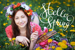 Young woman enjoying smell in a flowering spring garden with letters Hello sprint Stock Image