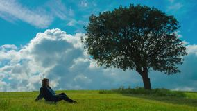 Young woman enjoying solitude under green tree. Relaxation alone with nature. Stock footage stock video