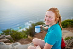 Young woman enjoying some coffee on a morning hike Stock Photo