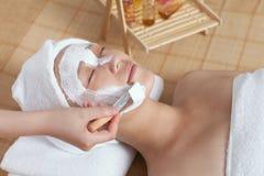 A young woman enjoying spa mask. A young women enjoying facial mask at spa salon, indoors Royalty Free Stock Photography