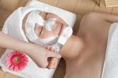 A young woman enjoying spa mask. A young women enjoying facial mask at spa salon, indoors Royalty Free Stock Image