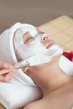 A young woman enjoying spa mask. A young women enjoying facial mask at spa salon, indoors Stock Image