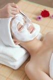 A young woman enjoying spa mask. A young women enjoying facial mask at spa salon, indoors Stock Images