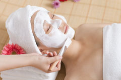 A young woman enjoying spa mask. A young women enjoying facial mask at spa salon, indoors Stock Photos